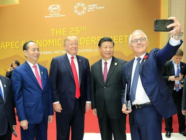 尷尬的是,當時越南國家主席陳大光(左)就站在川普(左二)身旁,看著滕博爾(右)的手機鏡頭並露出微笑,沒想到他最後竟然沒有被拍進去。(法新社)