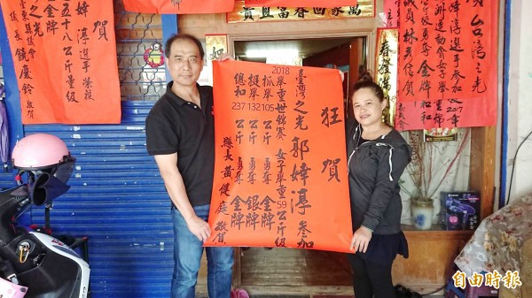 Taitung County Education Department Director Chang Chih-ming, left, holds a congratulatory message and medal tally with Taiwanese weightlifter Kuo Hsing-chun's mother at her home in Taitung County yesterday. Photo: CNA, courtesy of the Taitung County Government