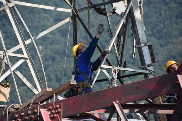 搶修工人頂著大太陽攀塔進行鐵塔組立工作,雖然悶熱難耐,但為了安全還是必須穿著長袖長褲。(經濟部提供)