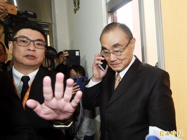 國防部長馮世寬一早前往總統府開會,因而晚到立法院。馮到立院備詢時,向主席請假到會議室外打電話關心總統府會議進度。(記者方賓照攝)
