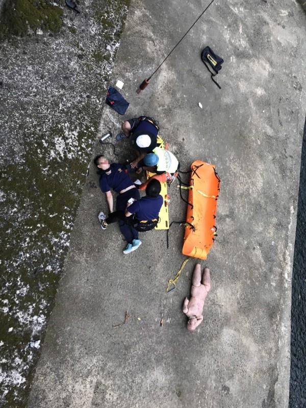 新竹縣政府消防局第二大隊今午在竹東鎮舉行常訓,陳姓隊員疑不慎踩到青苔,自5公尺高的平台跌落水溝邊,造成左手臂開脫臼及左大腿骨折,所幸意識清楚,沒有大礙。(記者廖雪茹翻攝)