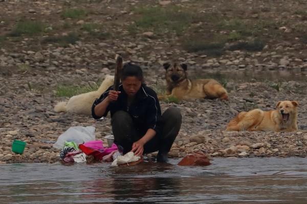 北韓婦女在鴨綠江畔洗衣服。(路透)