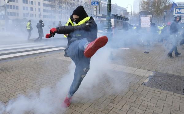 11月30日,比利時布魯塞爾市中心出現數百名身著黃背心的示威者,抗議行動最終演變成暴力活動,抗議者不僅焚燒警車洩憤,還向警方投擲煙霧彈和石塊。(歐新社)