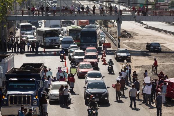 面對油價暴漲,上百民眾在墨西哥市區發起示威抗議,把車子開到公路及加油站堵塞交通,卻演變成暴力衝突。(法新社)