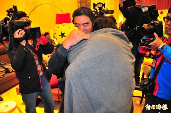 地震後受困的統帥飯店員工陳明輝,7日清晨獲救,他的兒子聞訊抱著孫子跑來飯店,祖孫三人相擁。(記者花孟璟攝)