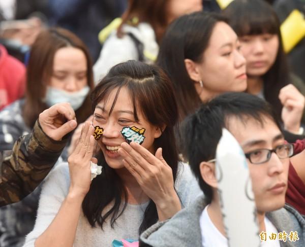 柯文哲选前之夜,支持者在脸上贴小贴纸。(记者方宾照摄)