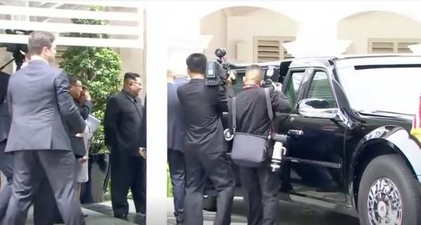 川普示意美方人員打開右側車門,與金正恩站在車旁對話,金正恩則微笑著向車內探望。(路透)