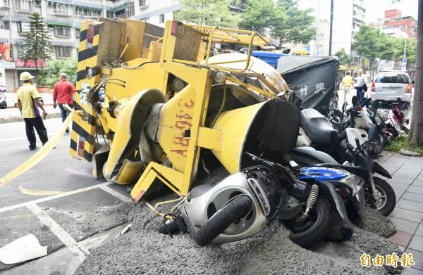 水泥車翻覆,壓毀停在路邊汽機車。(記者羅沛德攝)