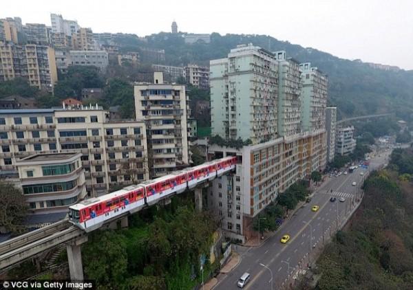 中國重慶市輕軌在移動過程中,會直接開進一棟19層高的大廈裡。(圖擷自《每日郵報》)