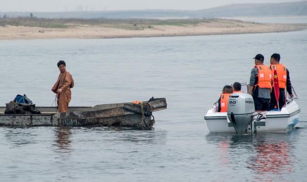 有一部份中國遊客改搭小船,和北韓漁民接觸。(法新社)