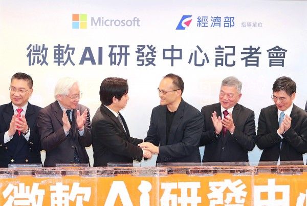 Premier William Lai, third left, and Microsoft corporate vice president David Ku, third right, shake hands at a news conference in Taipei yesterday. Photo: CNA