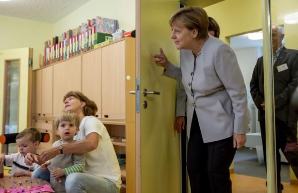 德國柏林從昨日起取消所有學齡前教育設施的費用,幫爸媽們每月節省數百歐元支出。圖為2016年德國總理梅克爾(右)訪問柏林1間托育機構。(資料照,歐新社)