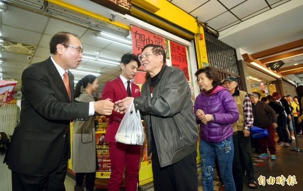 台彩總經理蔡國基與代言人阿ken發紅包。(記者方賓照攝)