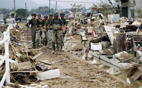 西日本暴雨造成多地災情慘重,警方、自衛隊和消防等部門至今派出7萬人以上,在酷暑下繼續搜尋失聯者並展開救援行動。(美聯社)