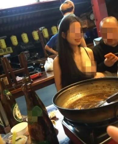 女子吃薑母鴨露出雪乳。(圖擷自「黑色豪門企業」臉書)