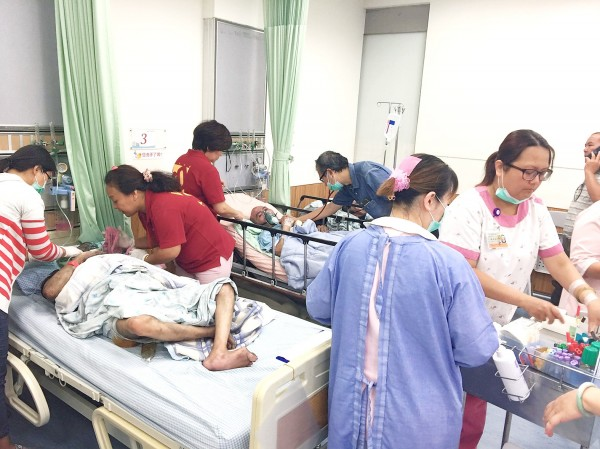 Medical staff yesterday attend to patients at a hospital in Pingtung County after a fire broke out at a private nursing home. Photo: Tsai Tsung-hsien, Taipei Times