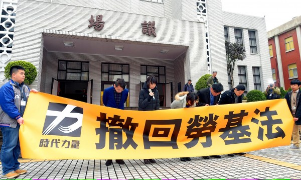 New Power Party lawmakers bow in apology outside the Legislative Yuan in Taipei on Tuesday for failing to stop the amendments to the Labor Standards Act. Photo: Chang Chia-ming, Taipei Times