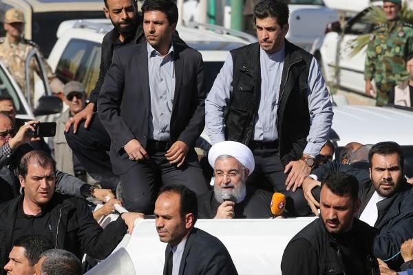 伊朗總統羅哈尼(中間白色頭巾者)週二到訪薩爾波勒扎哈卜視察災情。(法新社)