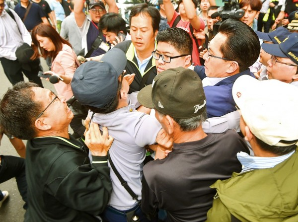 Democratic Progressive Party Legislator Tsai Yi-yu, center, wearing glasses, is pushed around by demonstrators as he tries to enter the Legislative Yuan in Taipei on Wednesday. Photo: Fang Pin-chao, Taipei Times