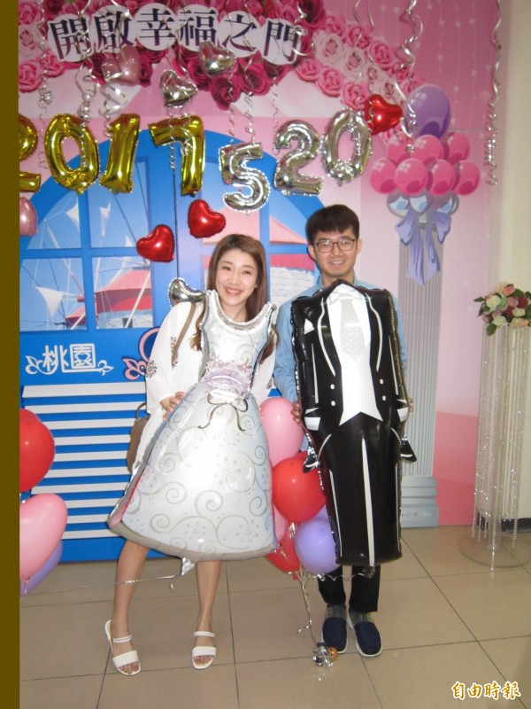 辦理結婚登記的新人們使用各種道具拍下甜蜜照片。(記者謝武雄攝)