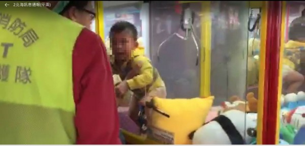 新北市樹林一名男童爬入大型夾娃娃機受困,消防員到場,通知業者開鎖化解虛驚。(記者吳仁捷翻攝)