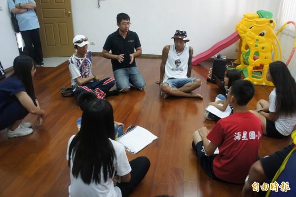 健志沒有天團架子,直接席地而坐,與保護學童聊天。(記者劉禹慶攝)