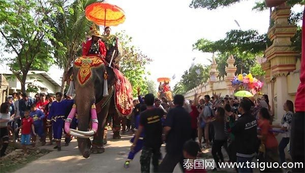 泰国女富商乘大象,沿街撒钱做功德。(取自《泰国网》)