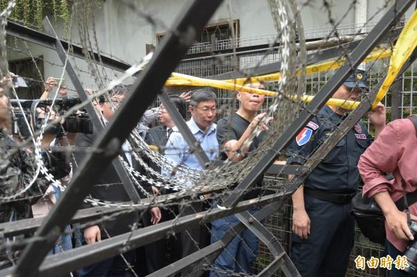 台北市長柯文哲(中)19日赴立院出席前瞻基礎建設公聽會,並提出簡單報告後,在警力戒護下,穿越重重拒馬才得以脫身。(記者張嘉明攝)