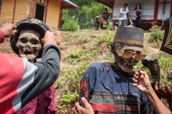 印尼蘇拉威西(Sulawesi)島上每年8月時,居民會挖開墳墓,將死去親人的屍體取出,為他們盛裝打扮,帶著他們遊街返家團聚。。(圖擷取自網路)