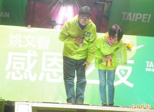 姚文智(左)攜同夫人潘瓊琪(右)一同向支持者鞠躬致意。(記者王藝菘攝)