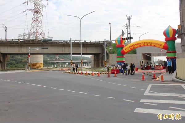 竹北沿河街車流在圖右通車點開通前,須從圖左黃色橋墩紅色禁止進入標誌前左轉,進入圖中有人的號誌桿下方車道,因此跟西向的車流發生衝突,形成一個危險的「髮夾彎」。(記者黃美珠攝)