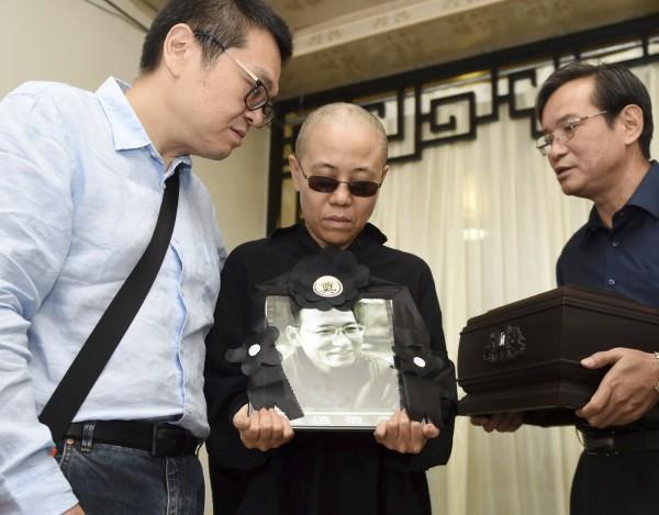 中國民主鬥士劉曉波病逝,中國當局趕在週六將他遺體火化,並在隨後舉辦簡易告別式。圖為劉曉波的妻子劉霞捧著劉曉波的遺照。(法新社)