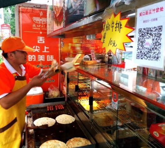 中國的煎餅攤販也會放上QR Code。(圖翻攝自《每日新聞》)