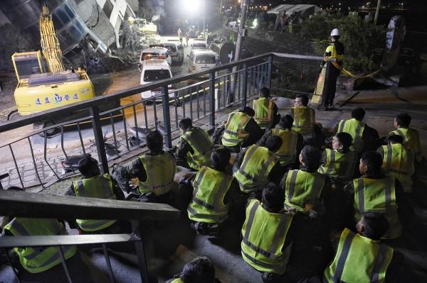 國軍協助搜救工作,搜救任務告一段落後在震災現場找一處席地而坐休息。(記者陳志曲攝)