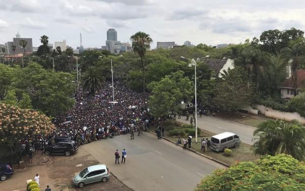 反穆加比的示威群眾直逼總統官邸,遭軍方阻擋而坐著抗議。(美聯社)