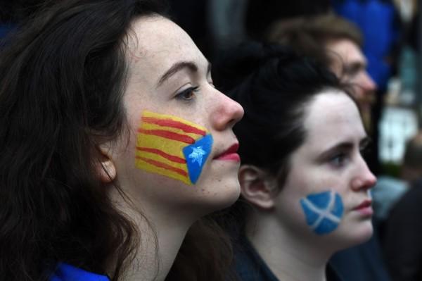 有人將加泰隆尼亞旗幟與蘇格蘭旗幟繪在臉上,象徵兩地的情誼。(法新社)