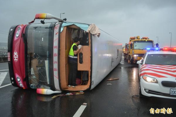 公路總局表示,不排除大客車全車強制繫安全帶。圖為去年10月梅姬颱風襲台,國道遊覽車被吹翻。(資料照,記者湯世名攝)