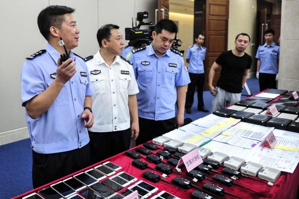 前年78名台灣人在亞美尼亞涉嫌電信詐騙遭遣送中國,中國廣州市花都區人民法院昨天對29名被告,做出一審判決。圖為廣東警方當時宣布偵破這起案件,示範嫌犯在詐騙過程中用對講機模擬警方辦公場所環境聲情形。(中央社)