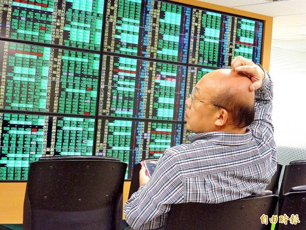 An investor watches a monitor at a brokerage in Taipei yesterday. Photo: David Chang, EPA