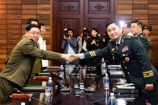 南韓今派出國防部北韓政策官員金度均(右),在上午跨越兩韓邊界率眾前往北韓開會,北韓方面則由陸軍中將安益山(左)帶領5人談判團迎接南韓人員。(法新社)