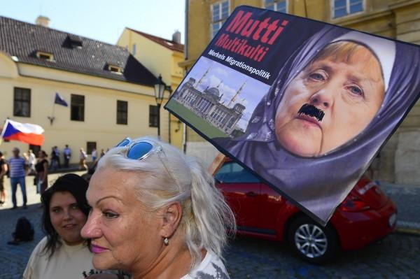 大批捷克民眾湧上布拉格街頭,抗議沒克爾的來訪以及她的難民政策。(美聯社)