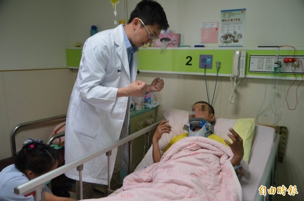 醫師黃裕涵請廖患者用力握拳。(記者陳鳳麗攝)
