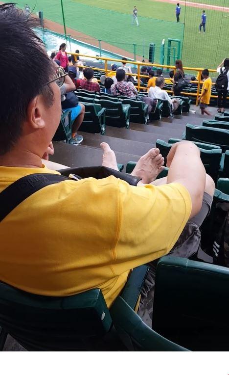 有網友在球場看到一名黃衣男子光著腳踩在前方椅背上。(圖擷自「爆料公社」臉書社團)
