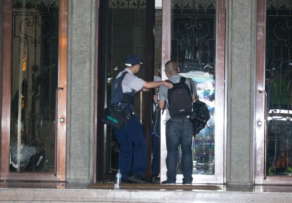 本報記者廖振輝(右)因採訪反黑箱課綱學生衝進教育部新聞,遭到警方留置,並禁止使用手機及相機,採訪工作被迫中斷,圖為廖振輝遭留置前被讀者拍下的畫面。(讀者提供)