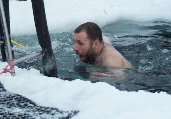 驻扎南极洲的科学家今日依照传统仪式,在摄氏零下22度的酷寒低温下,脱去上衣往冰水里面跳。(法新社)