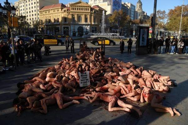 動保團體躺在巴塞隆納熱門購物區格拉西亞大道(paseo de gracia)上裸體陳抗。(法新社)