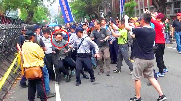 Peng Ke-wing, circled in red, a member of the Pension Reform Oversight Alliance, pushes Taoyuan Mayor Cheng Wen-tsan toward the barricades outside the Legislative Yuan in Taipei on Wednesday during a protest against pension reform proposals. Photo: copied by Wang Kuan-jen, Taipei Times