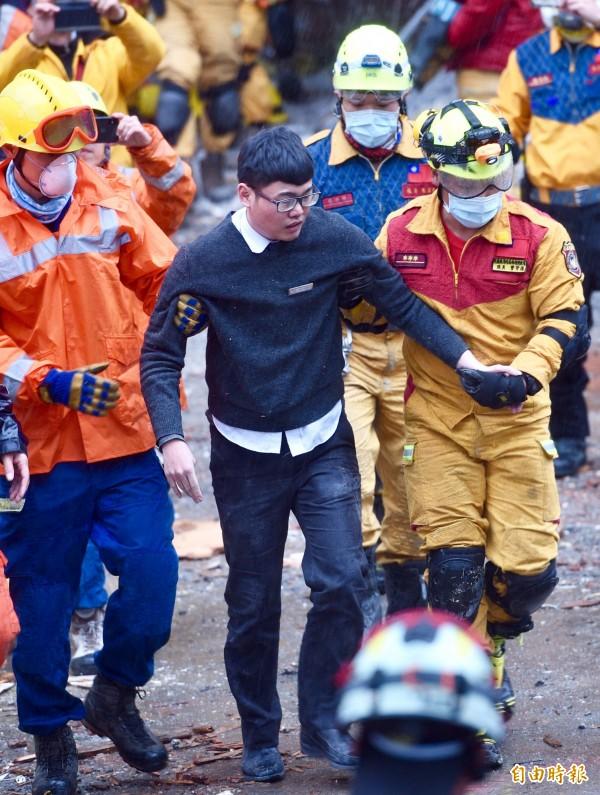 統帥飯店現場7日下午3點傳出好消息,飯店員工梁書瑋受困15小時後,在救難人員攙扶下步出建築物。(記者羅沛德攝)
