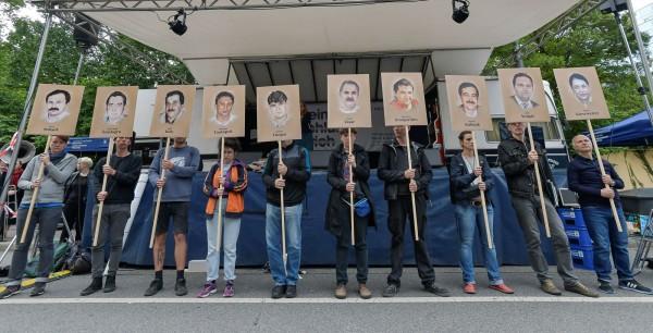 地下國社(NSU)在2000年至2007年間殺害了10人,而且以外來移民為主,其中包括8名土耳其裔與1名希臘裔的移民、1位德國女警。圖為示威者舉著繪有受害者肖像的抗議牌子。(法新社)