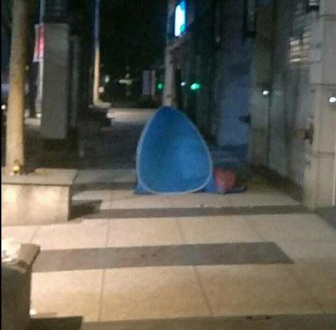 電信門市人員凌晨下班,卻發現門口有人搭帳篷夜宿街頭。(圖擷取自臉書「爆怨公社」)